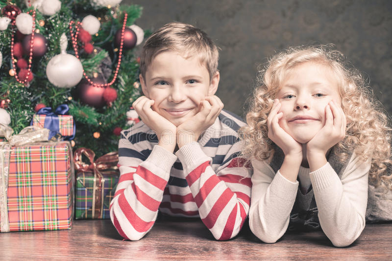 Menino e menina que encontram-se no assoalho sob a árvore de Natal imagens de stock