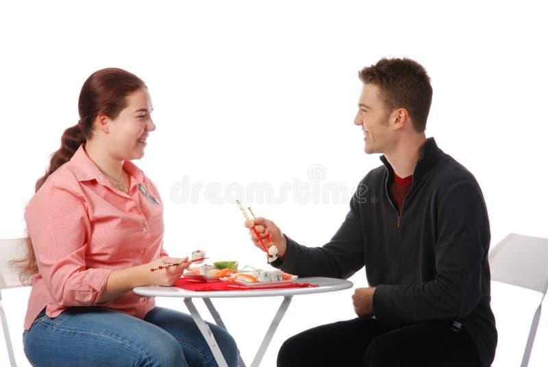 Menino e menina que falam e que comem fotos de stock