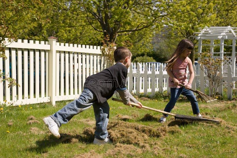 Menino e menina que fazem o yardwork fotos de stock royalty free
