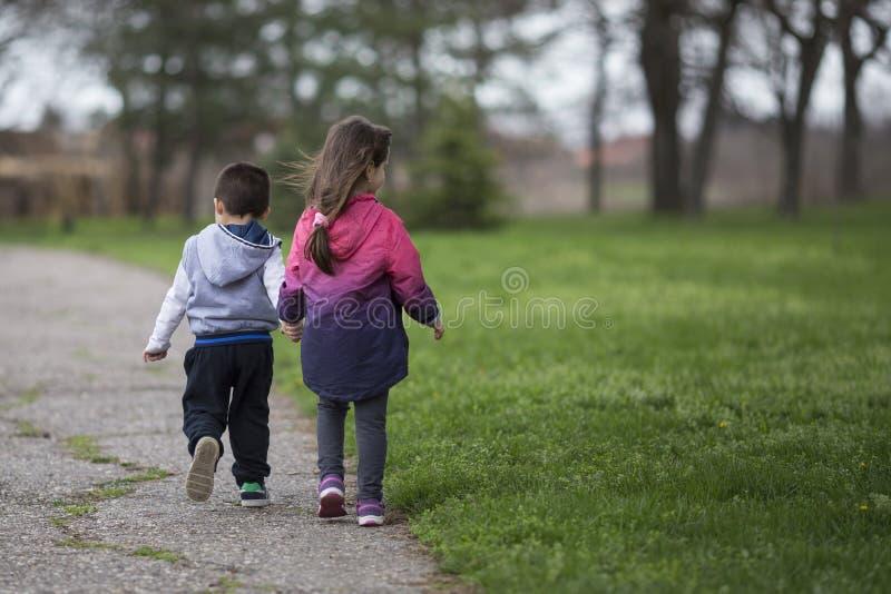 Menino e menina que guardam as mãos e que andam no parque fotografia de stock royalty free
