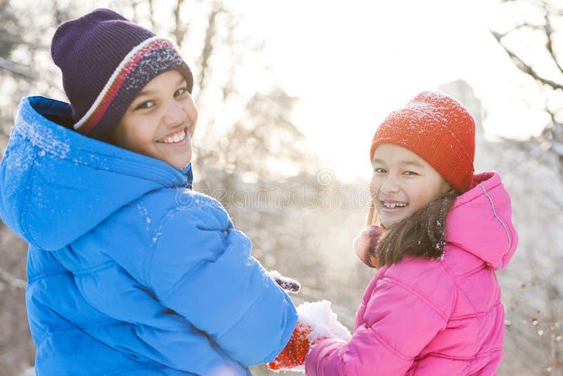 Menino e menina que guardam a neve nas mãos imagem de stock royalty free
