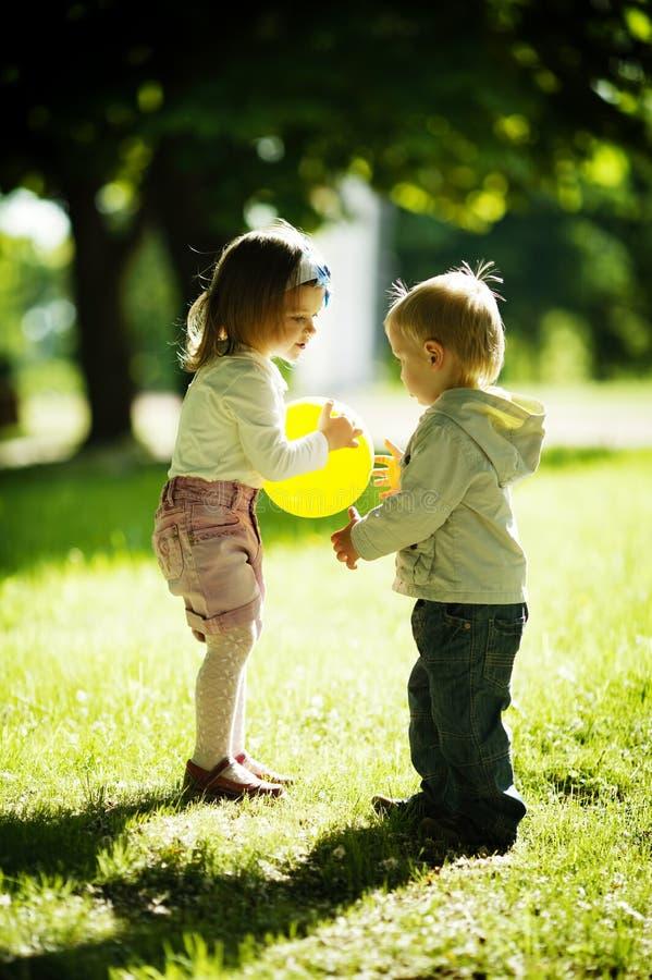Menino e menina que jogam com bola fotografia de stock royalty free