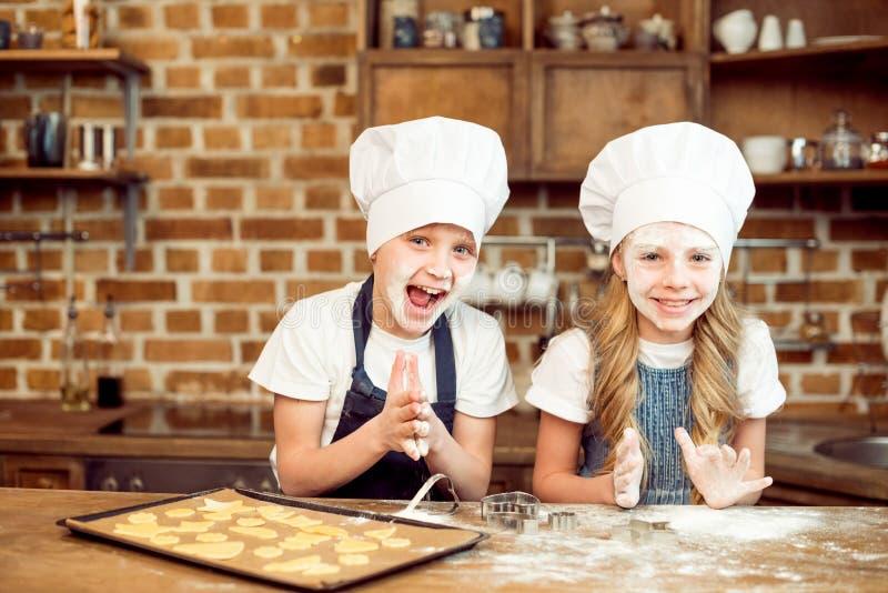 Menino e menina que jogam com farinha ao fazer cookies dadas forma fotos de stock royalty free