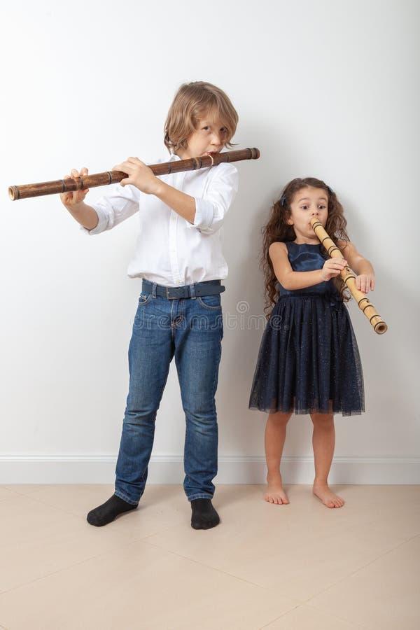 Menino e menina que jogam a flauta de bambu imagem de stock