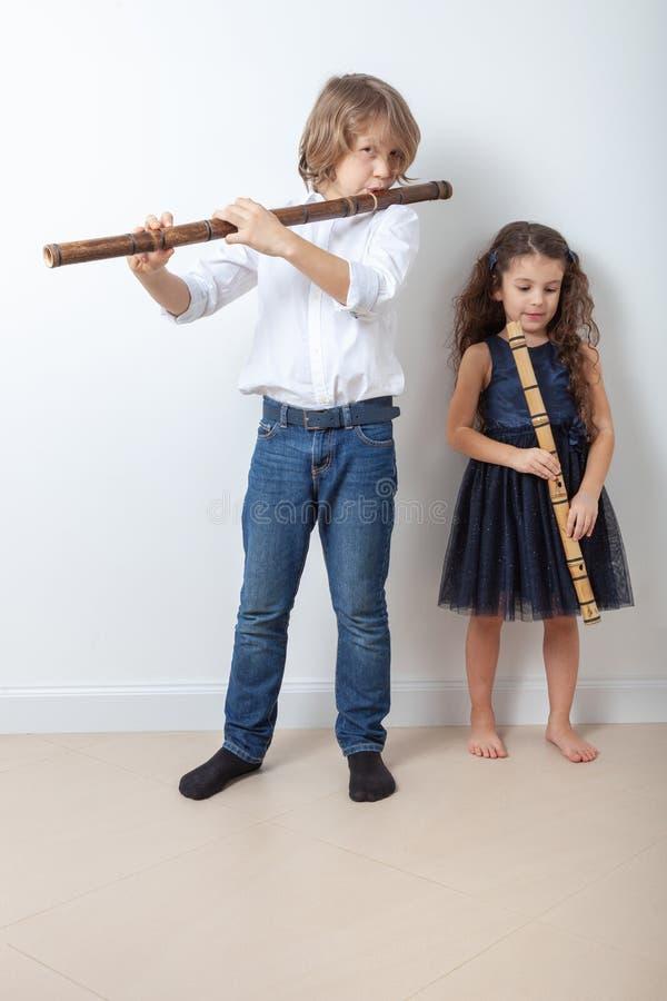 Menino e menina que jogam a flauta de bambu imagem de stock royalty free