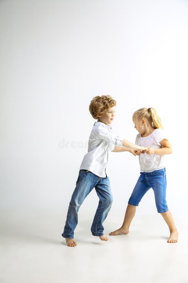 Menino e menina que jogam junto no fundo branco do estúdio fotos de stock