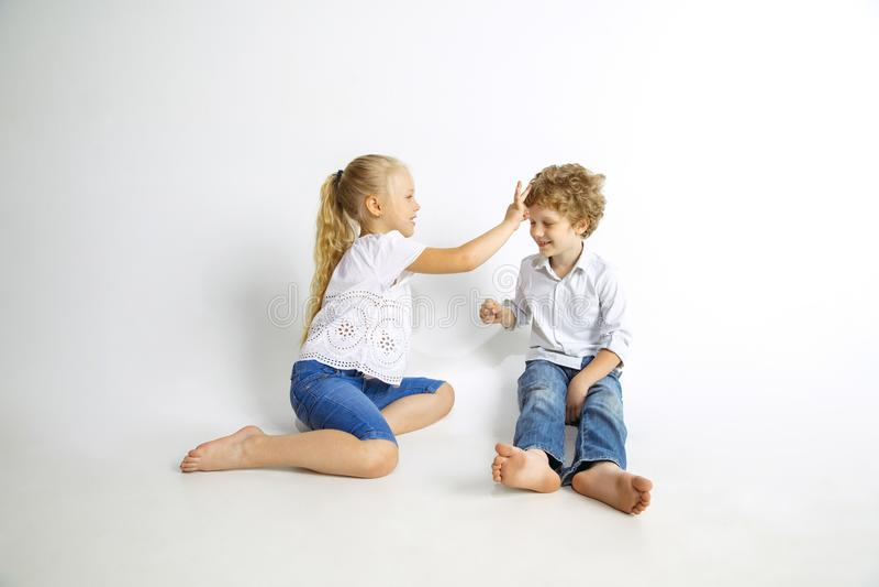 Menino e menina que jogam junto no fundo branco do estúdio fotos de stock royalty free