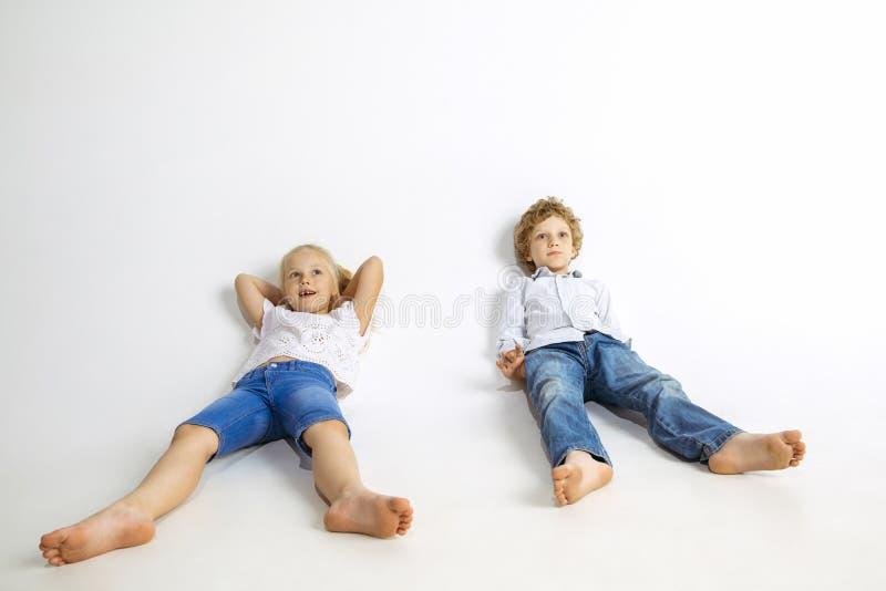 Menino e menina que jogam junto no fundo branco do estúdio imagens de stock royalty free