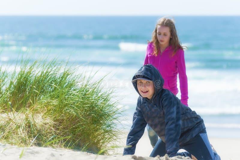 Menino e menina que jogam na praia litoral fotografia de stock royalty free