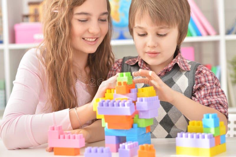 Menino e menina que jogam o jogo do lego imagem de stock royalty free