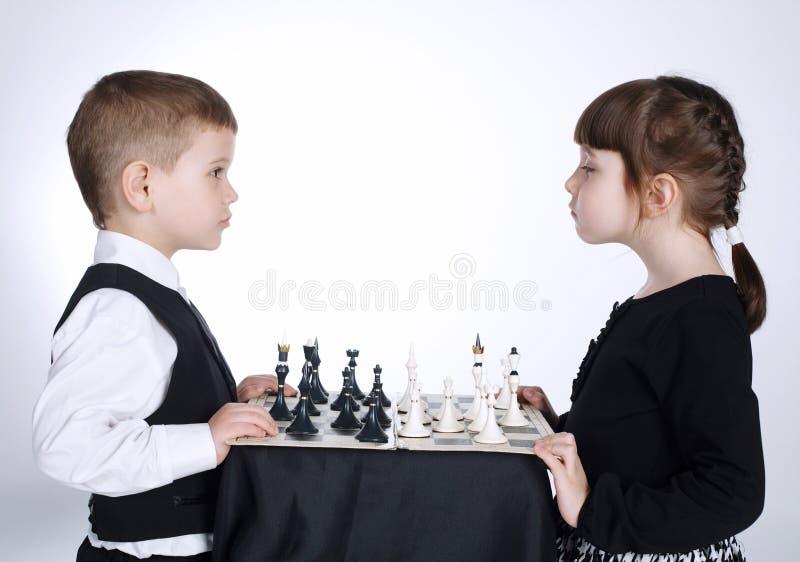Menino e menina que jogam a xadrez fotografia de stock