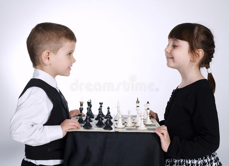 Menino e menina que jogam a xadrez fotografia de stock royalty free