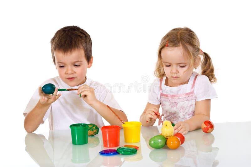 Menino e menina que pintam os ovos de easter foto de stock royalty free