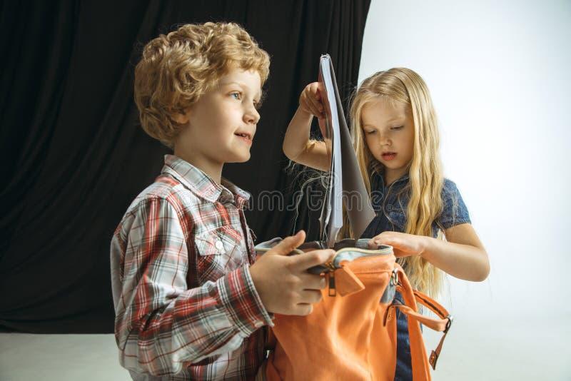 Menino e menina que preparam-se para a escola após uma ruptura de verão longa De volta ? escola fotografia de stock