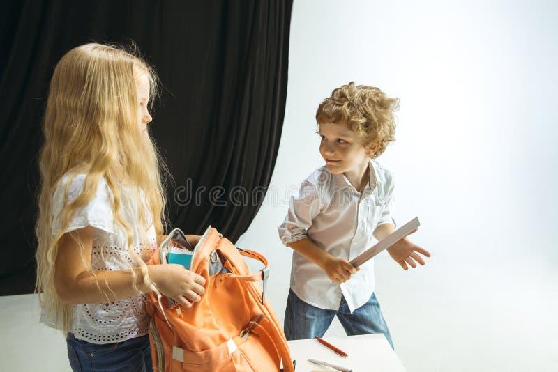 Menino e menina que preparam-se para a escola após uma ruptura de verão longa De volta ? escola imagem de stock