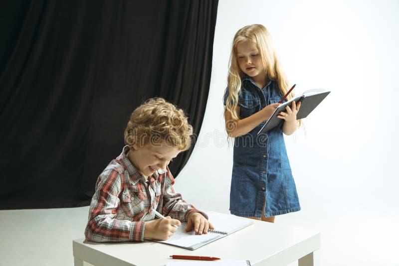 Menino e menina que preparam-se para a escola após uma ruptura de verão longa De volta ? escola foto de stock