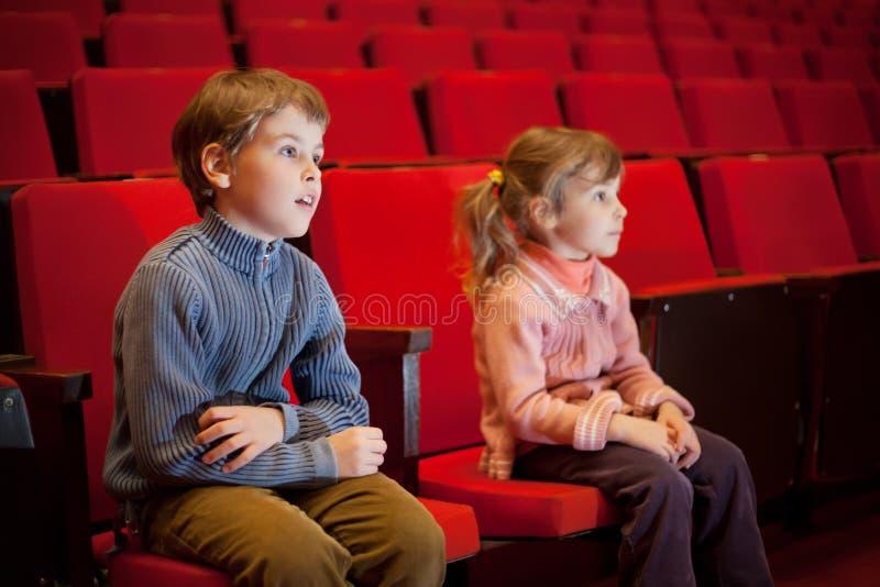 Menino e menina que sentam-se em poltronas no cinema fotografia de stock royalty free