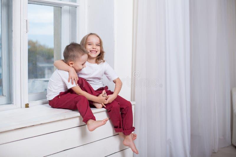 Menino e menina que sentam-se na soleira que olha para fora a janela imagens de stock royalty free