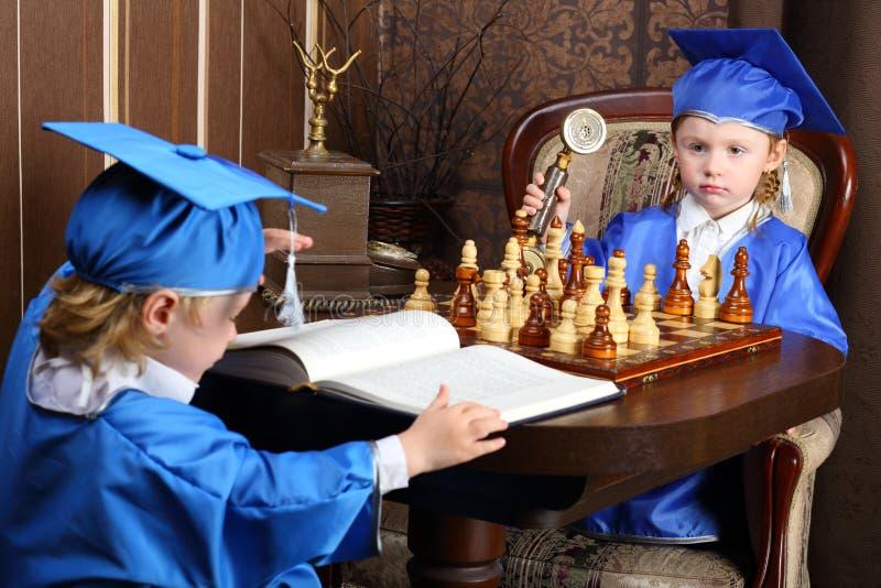 menino e menina que sentam-se na tabela da xadrez foto de stock royalty free