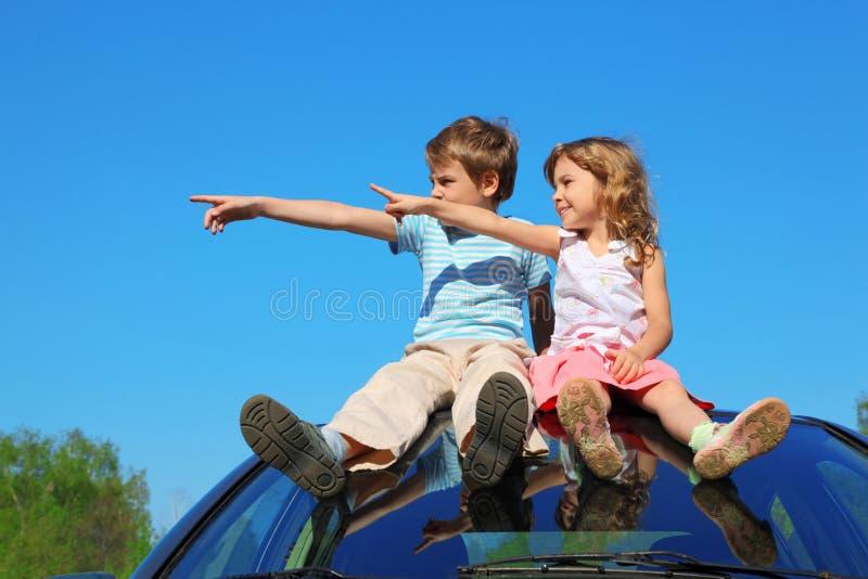 Menino e menina que sentam-se no telhado do carro imagens de stock royalty free