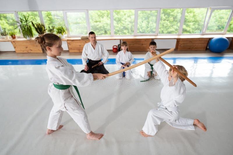 Menino e menina que têm a luta do aikido usando o jo fotografia de stock