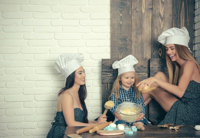 Menino e meninas em chap?us do cozinheiro chefe imagem de stock royalty free