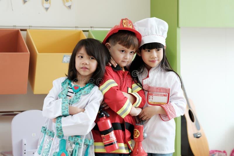 Menino e meninas que jogam como o occupat da polícia, do doutor e do cozinheiro chefe do bombeiro fotografia de stock