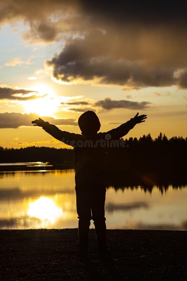 Menino e pôr do sol amarelo na Finlândia O menino mantém as mãos largas fotografia de stock royalty free
