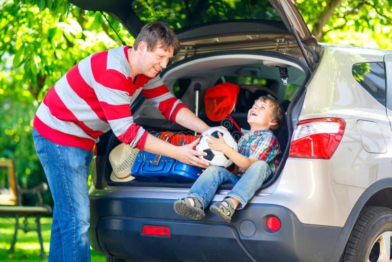 Menino e pai da criança antes de sair para férias do carro imagem de stock