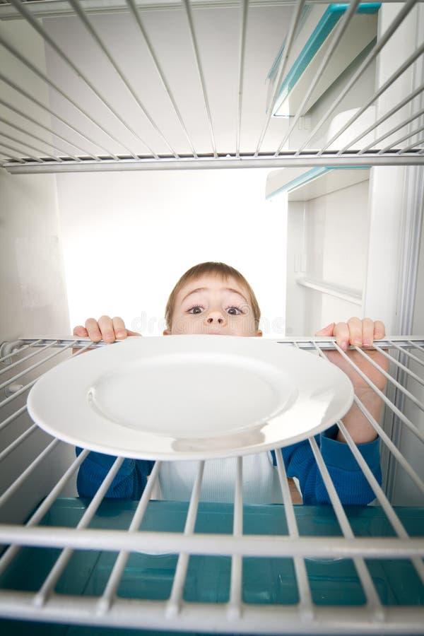 Menino e refrigerador vazio imagem de stock royalty free