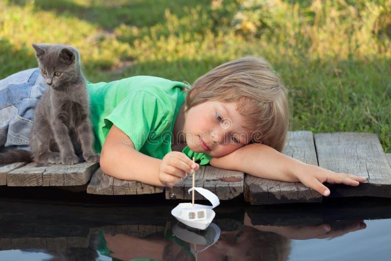 Menino e seu gatinho amado que jogam com um barco do cais na lagoa imagem de stock
