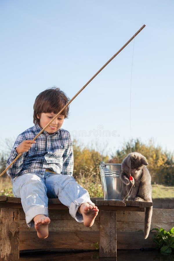 Menino e seu gatinho amado que jogam com um barco do cais na lagoa foto de stock royalty free