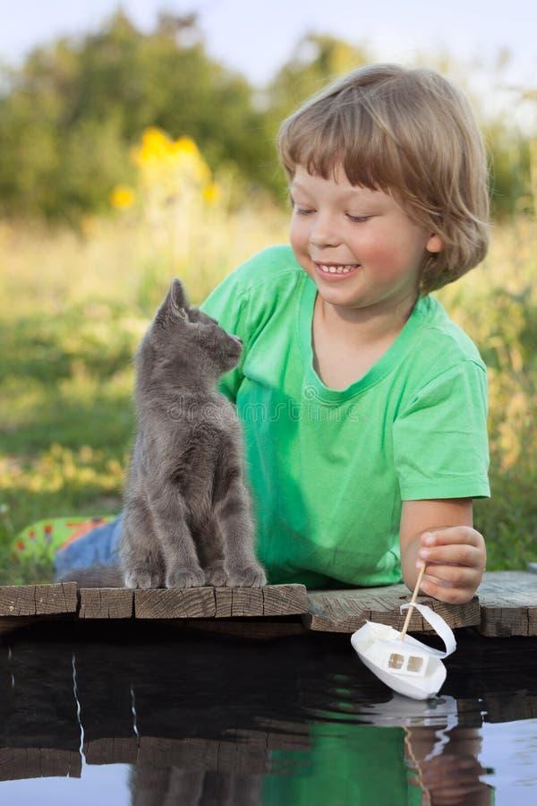Menino e seu gatinho amado que jogam com um barco do cais na lagoa fotografia de stock royalty free