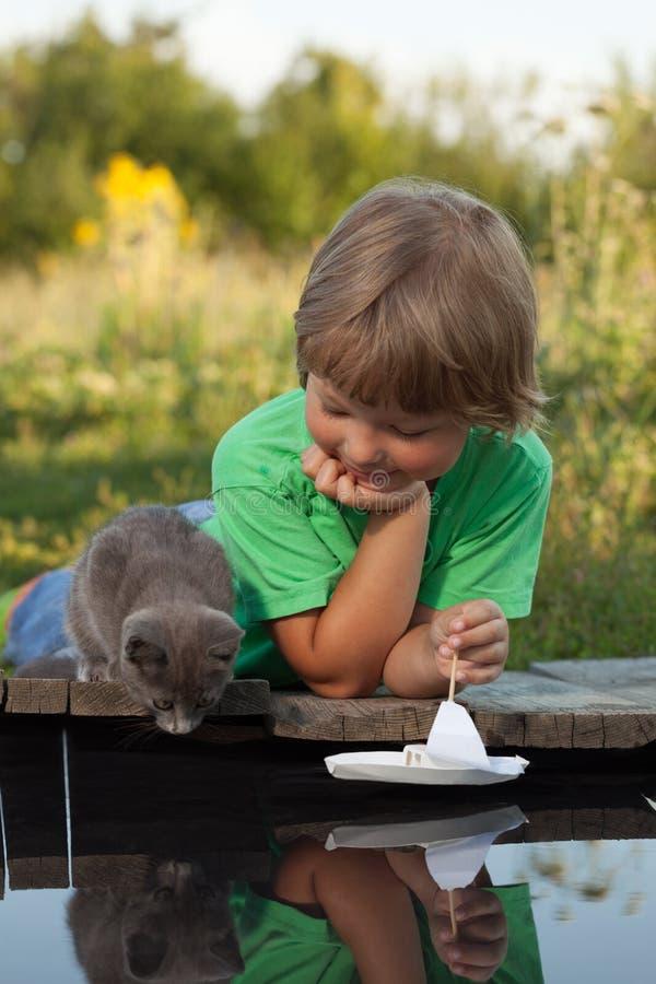 Menino e seu gatinho amado que jogam com um barco do cais na lagoa fotos de stock