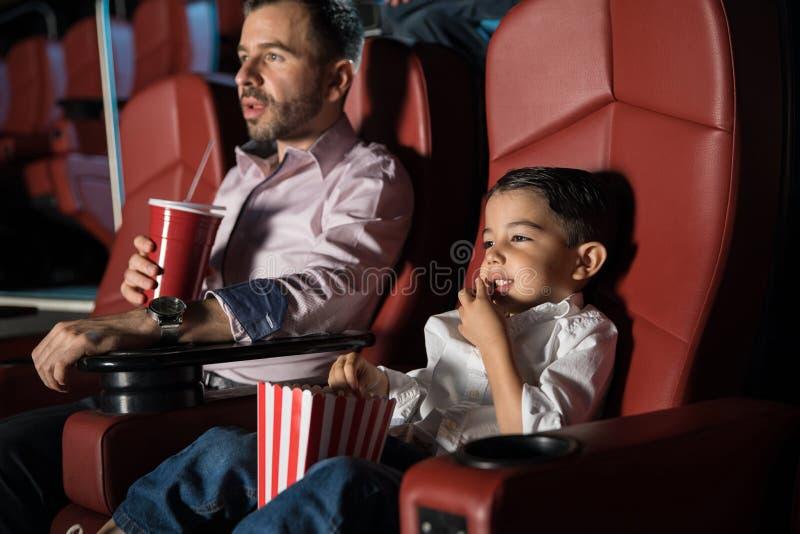 Menino e seu paizinho nos filmes fotografia de stock royalty free