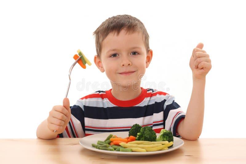 Menino e vegetais imagem de stock
