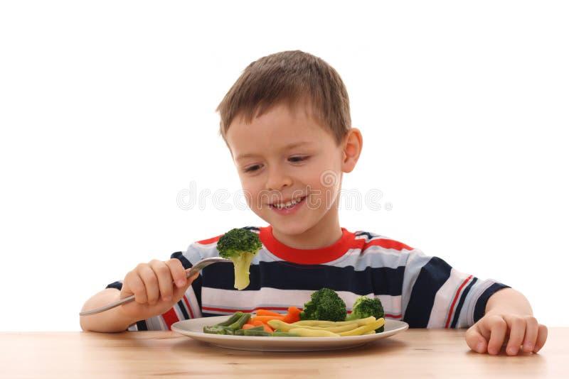 Menino e vegetais cozinhados imagens de stock royalty free