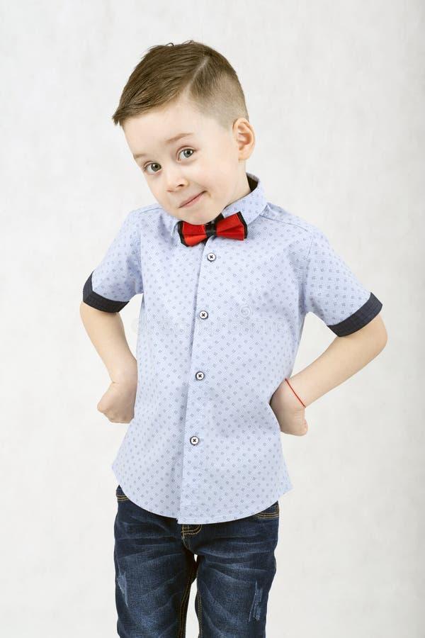 Menino elegante em um t-shirt branco e em suspensórios fotografia de stock