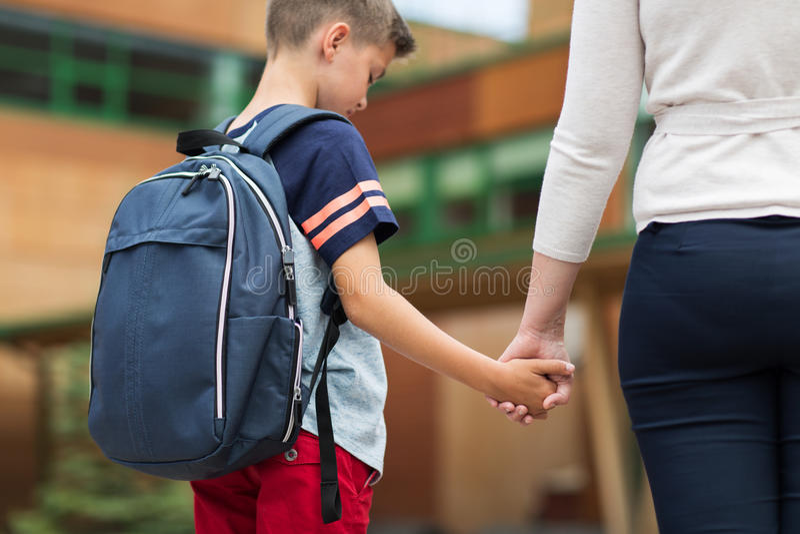Menino elementar do estudante com a mãe na jarda de escola imagem de stock royalty free