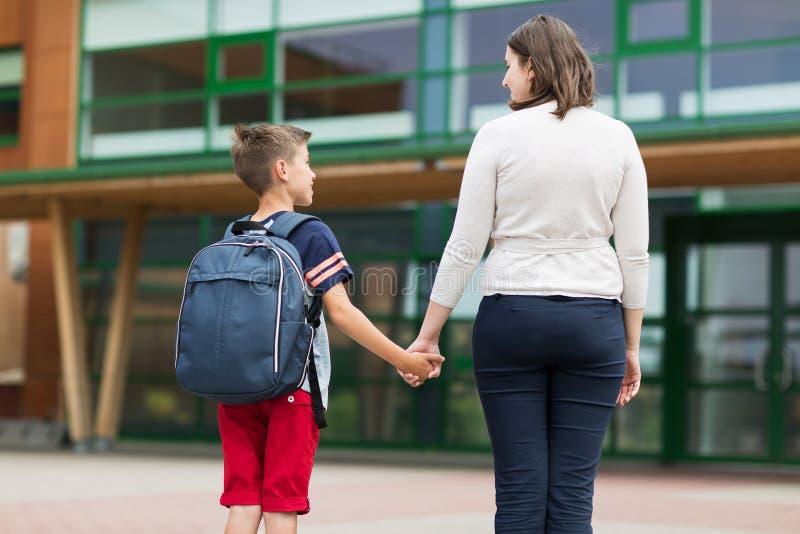 Menino elementar do estudante com a mãe na jarda de escola fotografia de stock