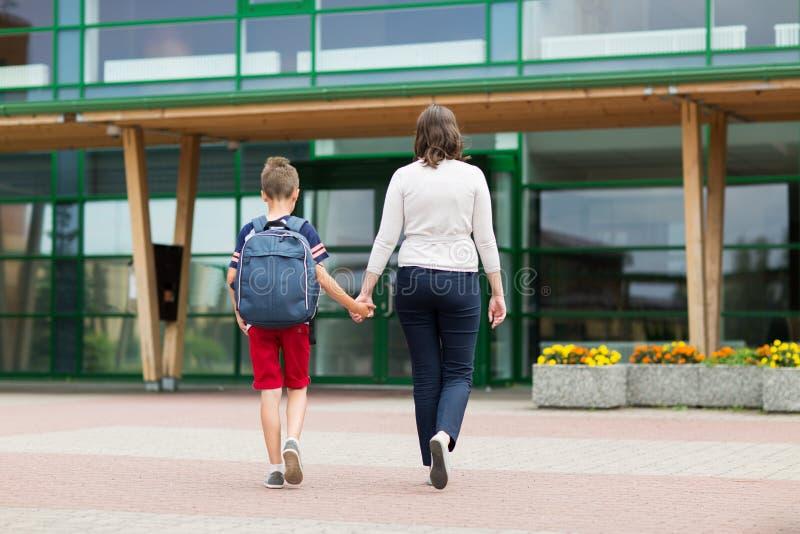 Menino elementar do estudante com a mãe que vai à escola fotos de stock royalty free