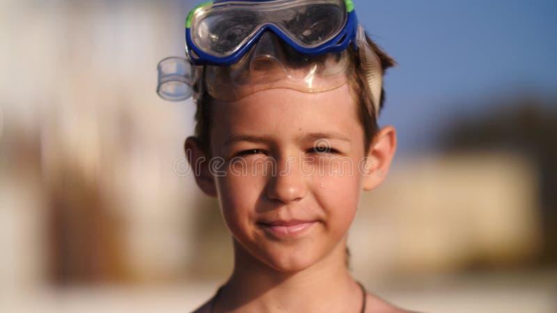 Menino em óculos de proteção nadadores na praia que olha a câmera e o sorriso imagens de stock