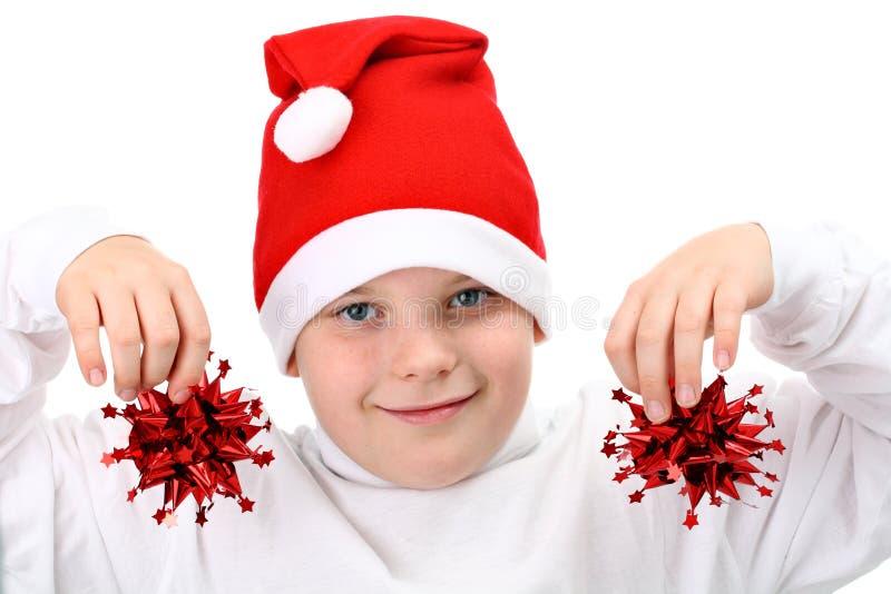 Download Menino Em Decorações Do Natal Da Terra Arrendada Do Chapéu De Santa Foto de Stock - Imagem de infância, tampão: 16867166