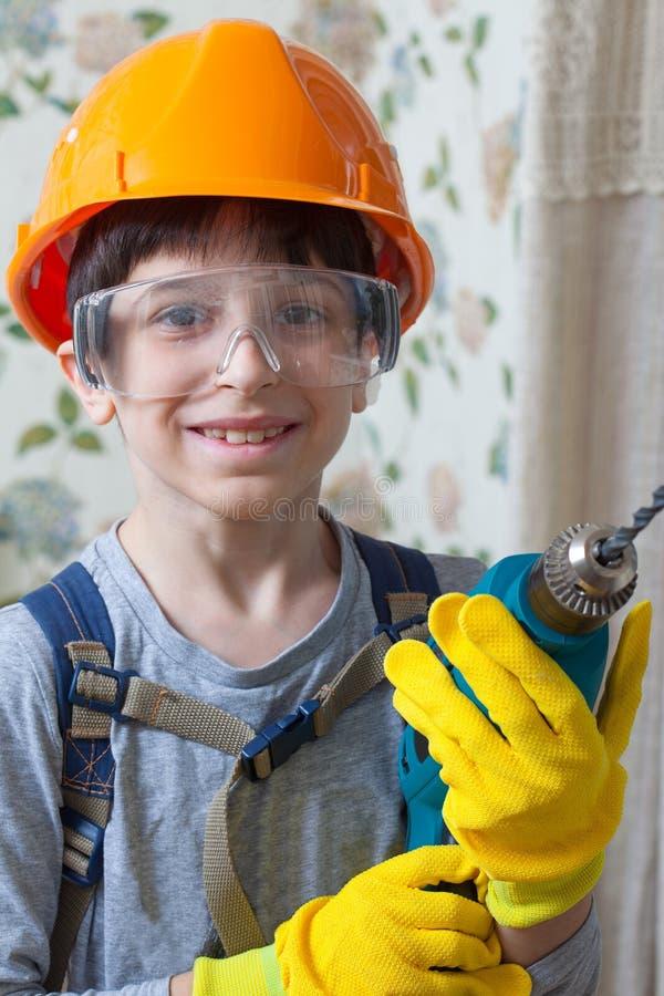 Menino em um capacete da construção e óculos de proteção de segurança com uma broca dentro suas mãos imagem de stock