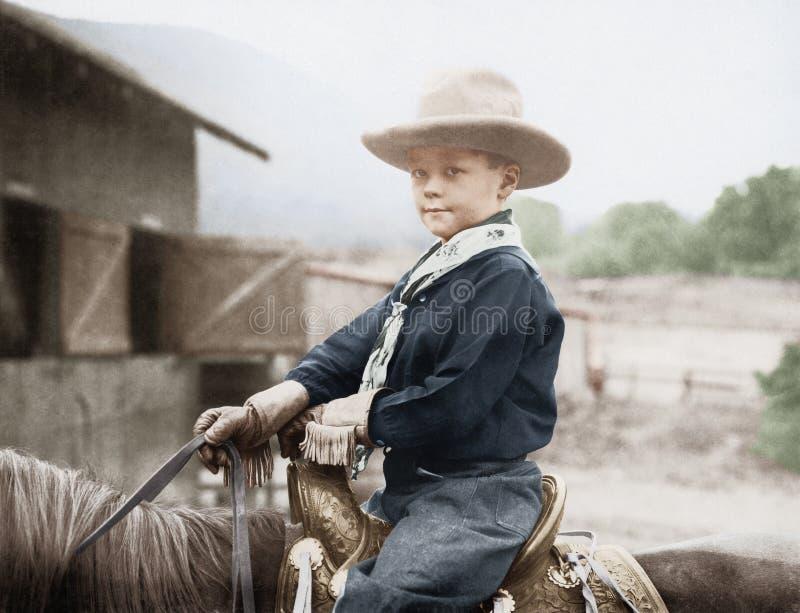 Menino em um chapéu de vaqueiro em um cavalo (todas as pessoas descritas não são umas vivas mais longo e nenhuma propriedade exis fotografia de stock royalty free