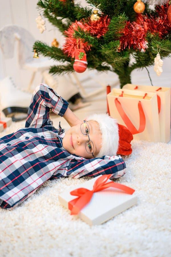 Menino em um chapéu vermelho do Natal que encontra-se no assoalho foto de stock