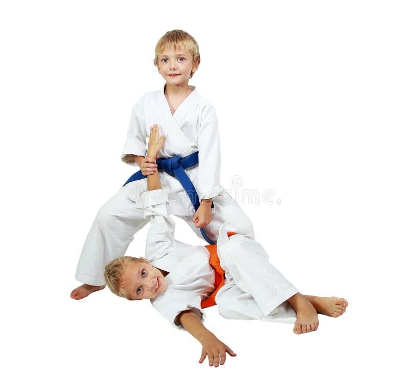 Menino em um quimono após a batida de jogo uma menina em um quimono fotos de stock royalty free