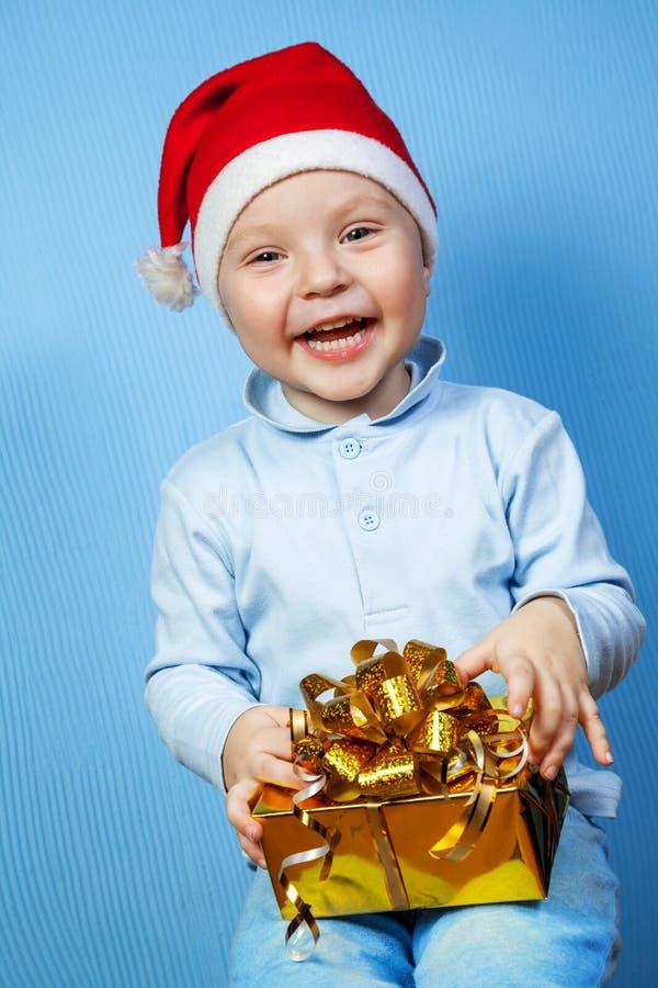 Menino em um tampão de Papai Noel com presentes imagens de stock royalty free
