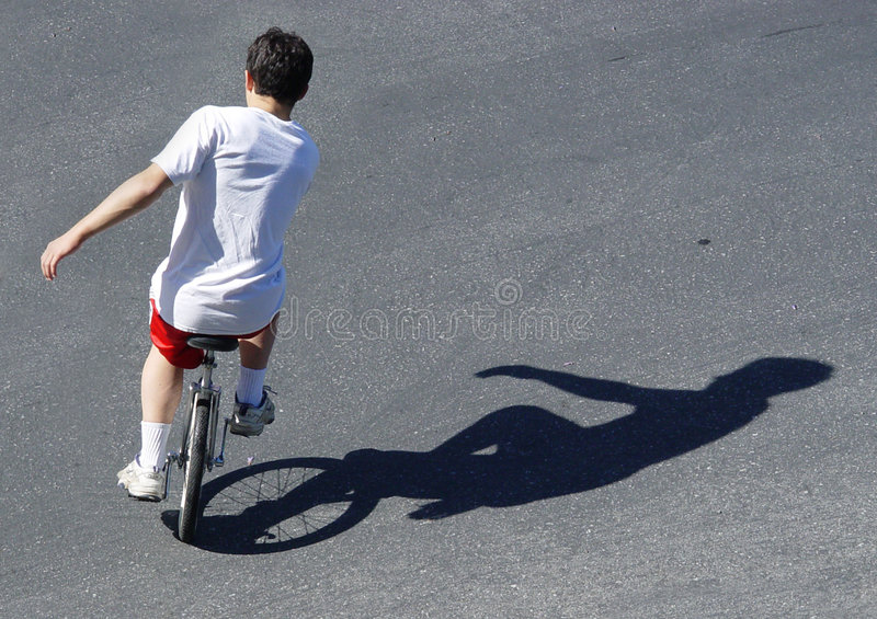 Menino em um unicycle fotografia de stock royalty free