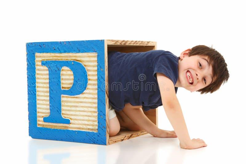 Menino em uma letra de bloco gigante P do alfabeto imagens de stock royalty free